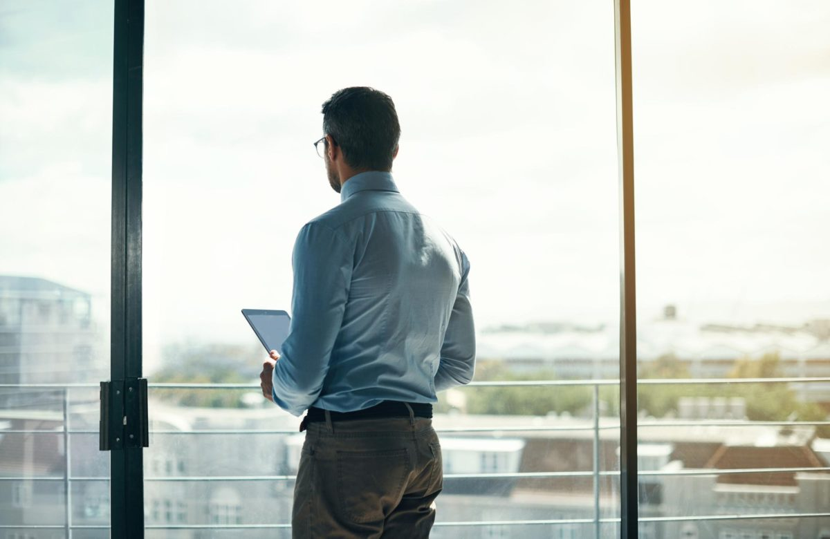 man at office window overlooking view