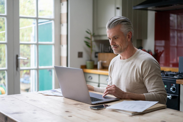 man in 50s reviewing retirement plan on computer