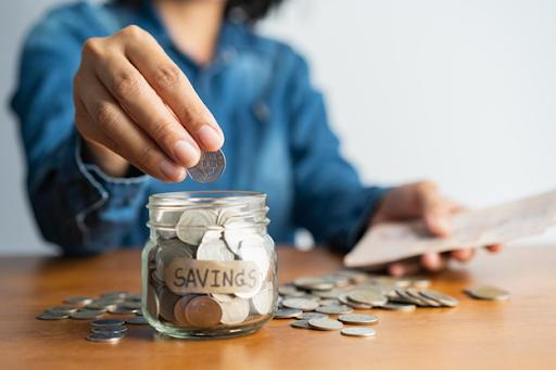 woman adding coins to retirement savings jar